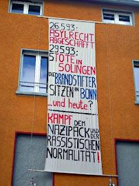 Hauswand mit Transparent: »26.5.93: Asylrecht abgeschafft. 29.5.93: 5 Tote in Solingen. Die Brandstifter sitzen in Bonn … und heute? – Kampf dem Nazipack und der rassistischen Normalität!«.