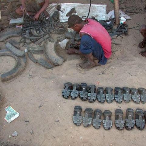 Making shoes out of old car tyres.