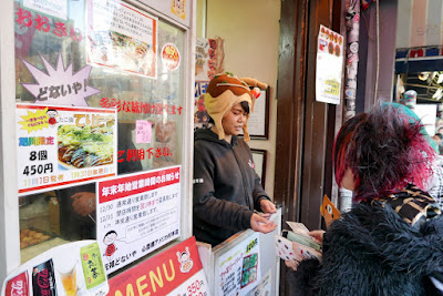 I went for the takoyaki stand Ganso-Donaiya with the famous rotating takoyaki sign. And the lady taking orders is wearing a hat. And there are photos from articles and a Tripadvisor sticker on it. Must be good!