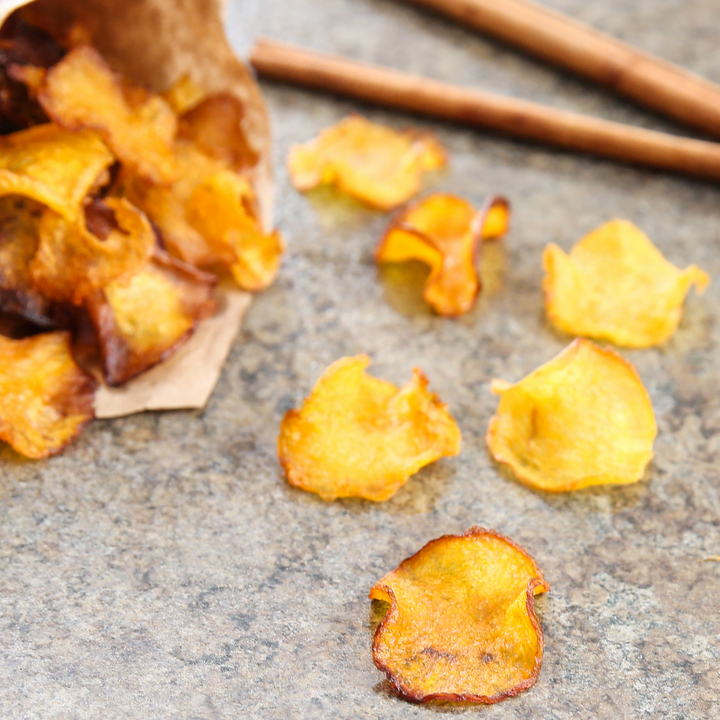a close-up photo of pumpkin chips with cinnamon sticks in the background