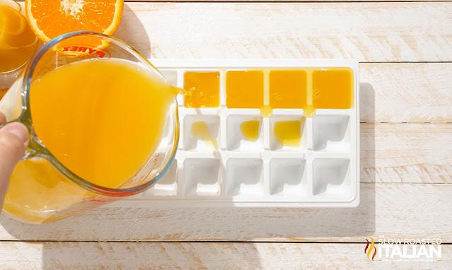 orange creamsicle - pouring orange juice into an ice cube tray