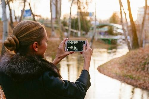 スマホで写真を撮る女性の後ろ姿