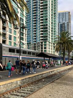 Mennesker som går på perrongen langs et toetasjers tog.
