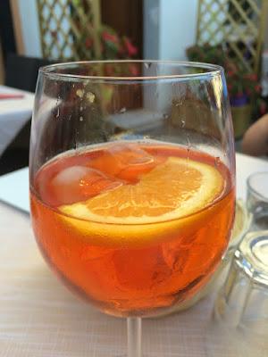 Et glass med orange drikke med appelsinskive oppi.