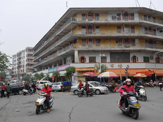motorbikes at an intersection with a large yellow building in Yangjiang, China
