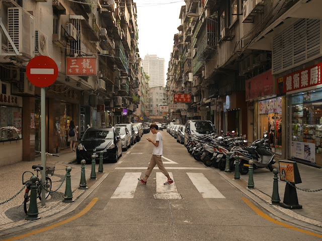 person walking with a mobile phone across Rua da Restauracao in Macau's Three Lamps District