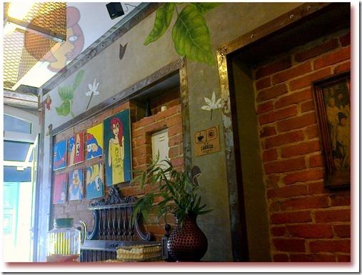 """Foto da parede da entrada da """"Fábrica - Coffee Roasters"""", contendo pintura com figuras da planta café na parede e quadros de super heróis alusivos ao beber café"""
