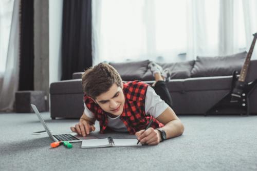 high school boy doing work on the floor