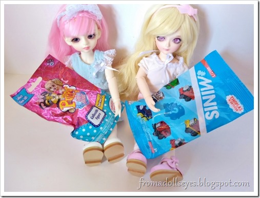 Two cute yosd sized ball jointed dolls holding packages for blind bag toys.  The pink haired bjd (Yuna) is holding a Puppy in My Pocket bag and the blond doll (Sakura) is holding a Thomas and Friends train bag.