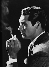Photo: Cary Grant, in profile. The suit is exquisite. Unlike female stars, there is no jewelry in sight, save a glimpse of a (very fine) watch.  The lighting again emphasizes the 3D modeling of the subject.