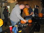 Pumpkins of all shapes and sizes had a slightly less enjoyable time than did the guests, as Aaron reaches for the saw.