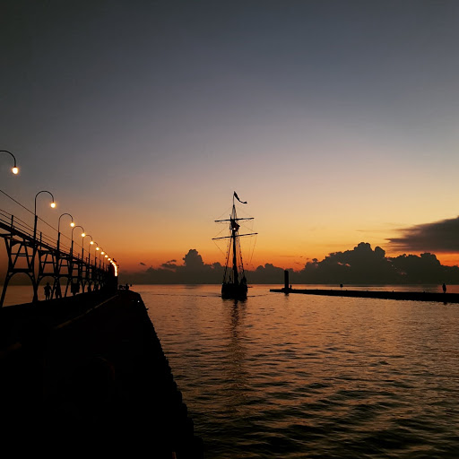 The Tall Ship Friends Good Will coming into port at sunset in South Haven, Michigan
