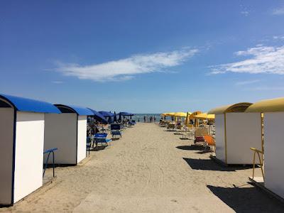 Små hus foran rader med parasoller på stranden.