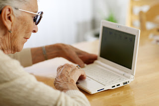 this elderly woman is attempting to navigate on a laptop computer