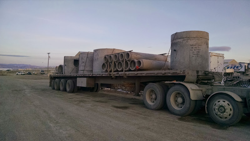 long flatbed trailer loaded with cement pipes and chained