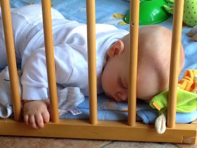 Baby schläft im Laufgitter