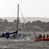 An ALB crew member has been transferred to the yacht to assist the 2 crew members aboard and secure a towline (the mast halyard) - 27 October 2013.  Photo credit: Mike Millard