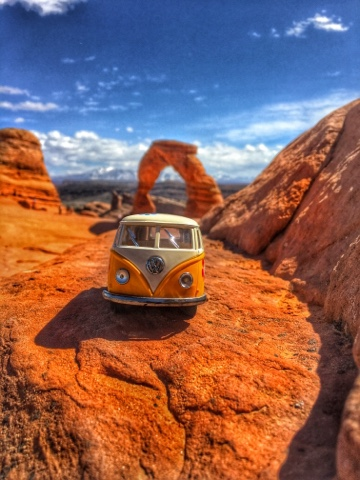 yellow volkswagen van in front of Delicate Arch in Arches National Park