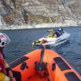 A 5.5m speedboat had picked up a pot buoy and fouled its propeller and an ILB crew member tries to untangle it. 1 September 2013 Photo: RNLI/Poole