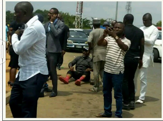 Senator Dino Melaye Sitting On The Ground While Resisting Arrest (Photo)