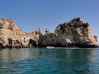 En liten båt med kurs mot en grotte i fjellsiden.