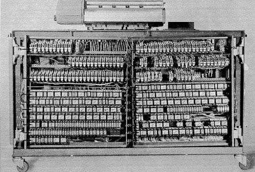 The IBM 403 accounting machine is controlled by hundreds of relays, many of which are mounted in the back of the machine. Photo from the Field Engineering Manual, fig 81.