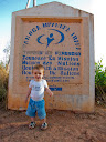 Matimu in front of the sign at the YWAM base outside Tana, where the leader of YWAM Madagascar is.