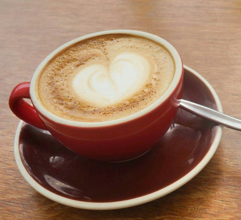 a cup of Flat White with a heart as its latte art