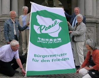 Gruppenfoto mit Flagge: Weiße Taube auf grünem Grund »Peace. Mayors for Peace. Bürgermeister für den Frieden«.