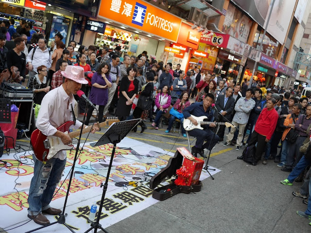 two men with guitars performing at Sai Yeung Choi Street South