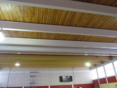 Painting of beams in high school gym ceiling almost complete
