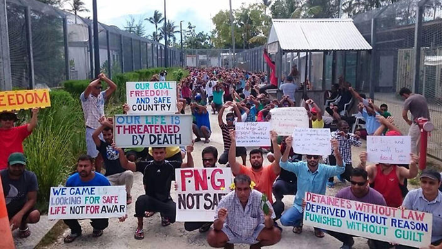 Refugees and asylum seekers holding up banners during a protest at the Manus Island immigration detention centre in Papua New Guinea. Photo: AAP