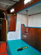 Photo: One coat of primer on pilot berth overhead and bulkhead.