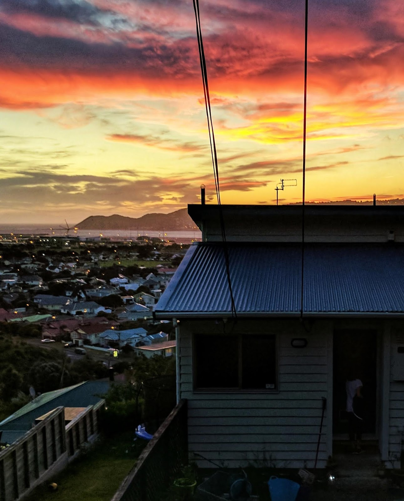 Sunset and house, looking out over Lyall Bay towards the South Island from Townsend Road, Miramar (Wellington, NZ)