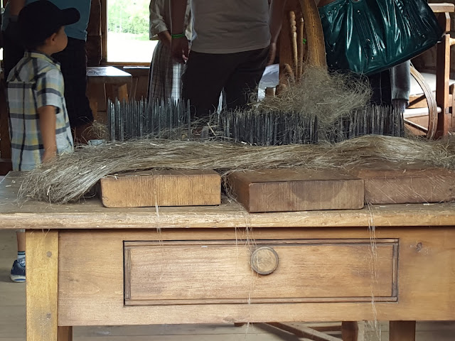 Carding flax to make thread. From Acadian History Comes Alive in a New Brunswick Village