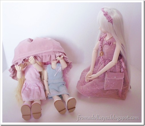 Two dolls hiding underneath some clothes.