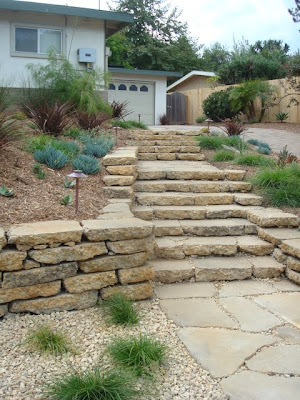 Our design added a generous stairway through the garden which welcomes visitors to the front door without forcing them to trudge up the driveway.