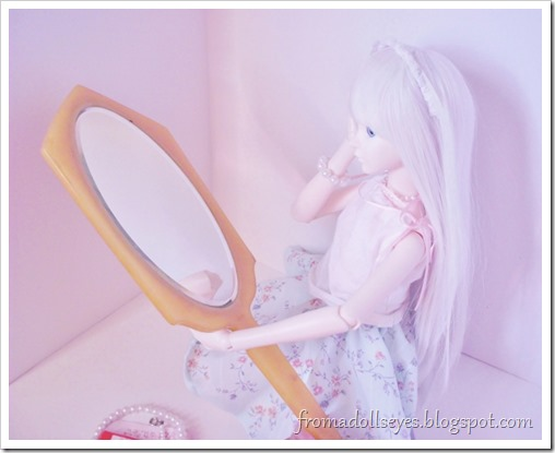 A doll holding a large hand mirror.