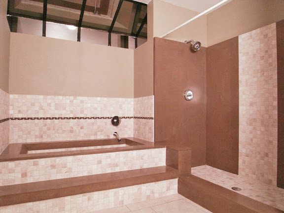 Sun Lakes AZ Realtors offer master bath with custom designed travertine and concrete bath/shower with inlaid custom tile work interwoven in design and Kohler high end fixtures