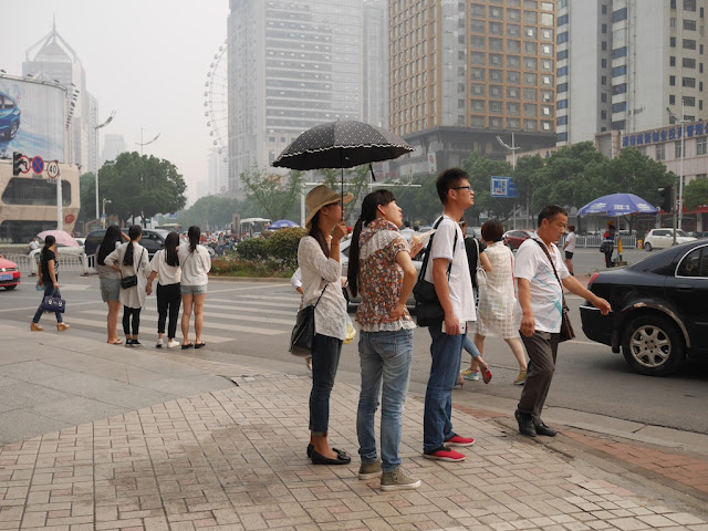 woman holding an umbrella at a street intersection in Changsha