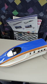 This is the Eki Bento I chose! I even brought it back from Japan and it sits on a shelf next to my other food vessels of a killer whale from SeaWorld from way back when and a Cars cone from Disneyland California. The color of this train matches the new in 2015 JR West's W7 Series Shinkansen train. On a test ride, it departed from Kanazawa Station for Nagano Station, hitting 260 kph in seven minutes