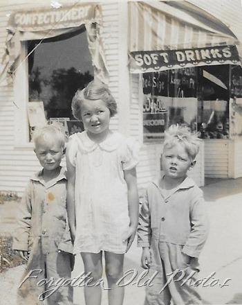 Three kids outside of a shop