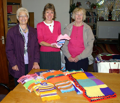 Gaye Eastwood and Margaret Brighmore present baby clothes and blankets from RSM Knitting & Nattering and AgeUK Knitters to Anne Symmons at World In Need. Oct 2012