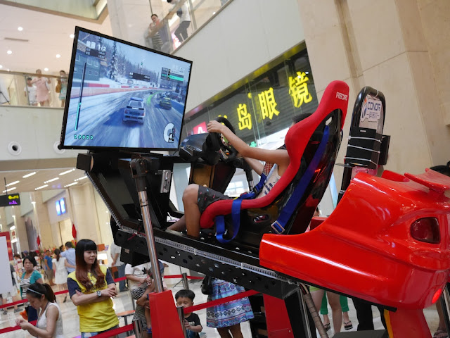 boy playing a moving car arcade game