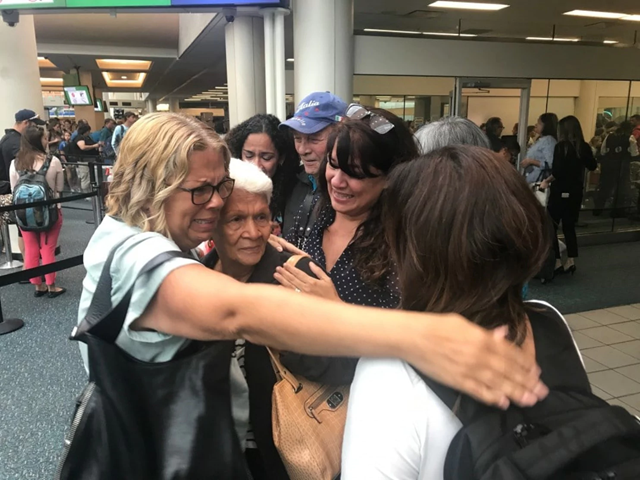 Leonor Figueroa, 82, center, a survivor of Hurricane Maria, is surrounded by her daughters after arriving at the Orlando airport from Puerto Rico in September 2017. Photo: Joel Achenbach / The Washington Post