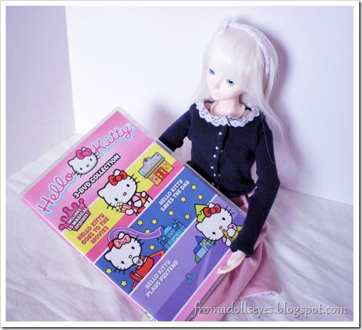 A bjd holding a Hello Kitty DVD, purchased from a thrift store.