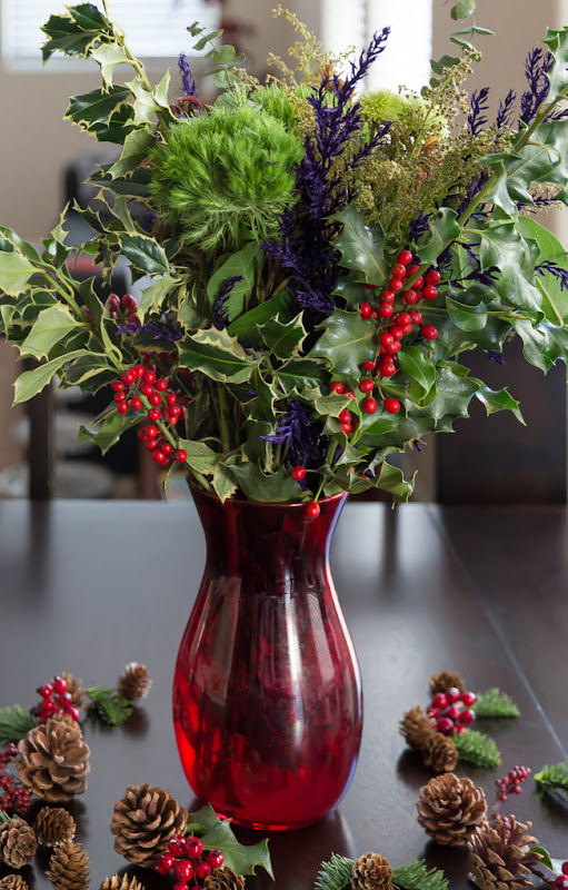 photo of a vase filled with holiday flowers and greenery