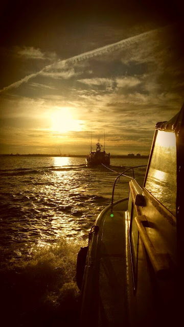 16 July 2014 - Poole ALB towing a 7m day boat with engine failure back to Poole in the setting sun Photo: RNLI Poole/Dave Bursey