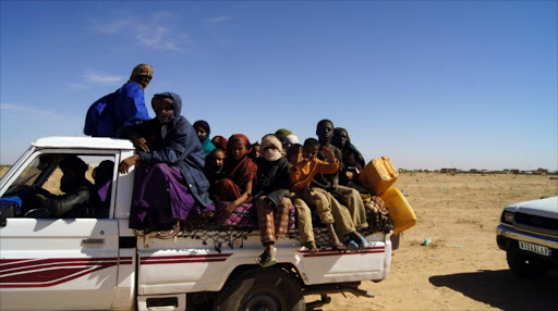 Malian refugees ride in the back of a truck transporting them on a dirt road from Timbuktu to the Mauritanian town of Fassala.