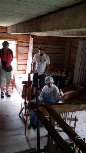 In this house, a historical re-enactor showed how to weave. Look at the low ceilings, dark room, and tiny bed! From Acadian History Comes Alive in a New Brunswick Village